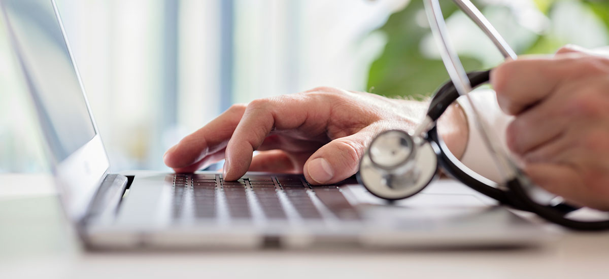 Close up of doctor using laptop, holding a stethoscope - Accerta