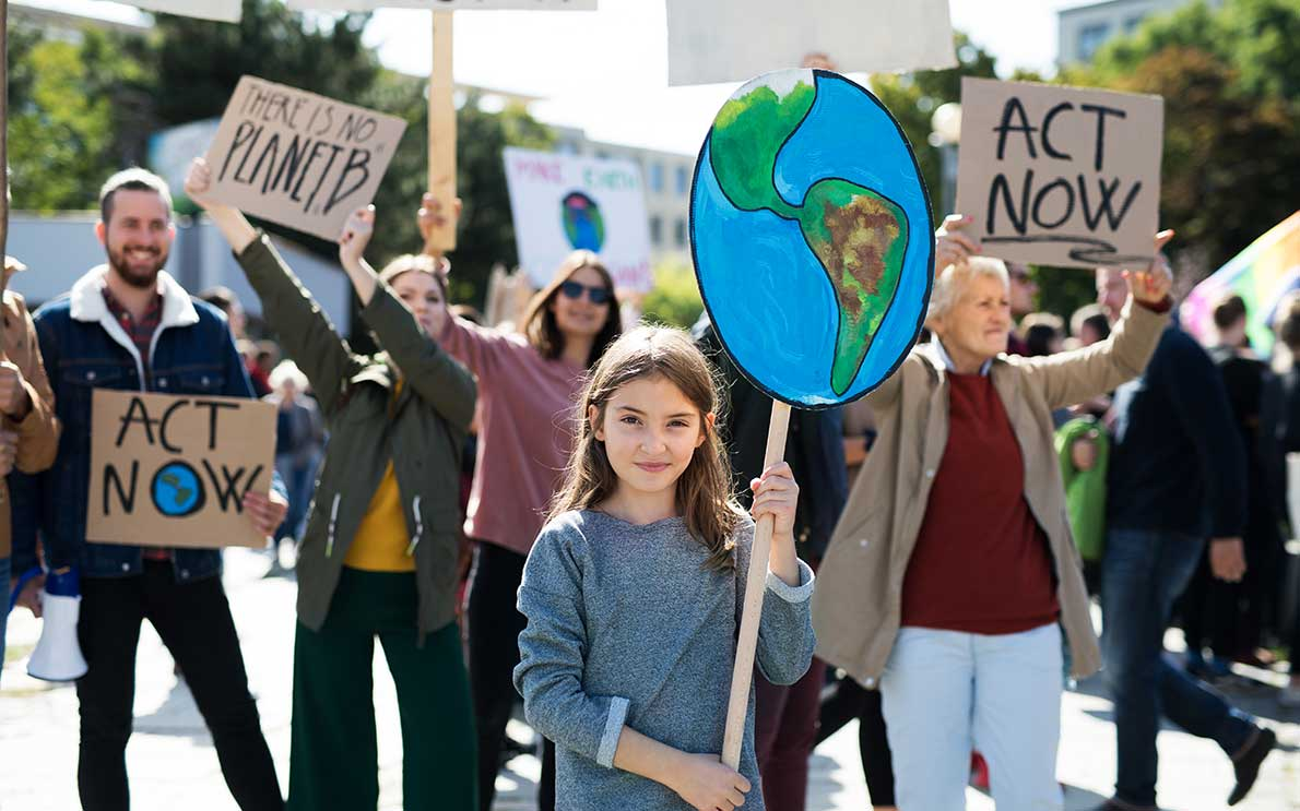 Young girl holding up cardboard Earth sign at environmental activism event