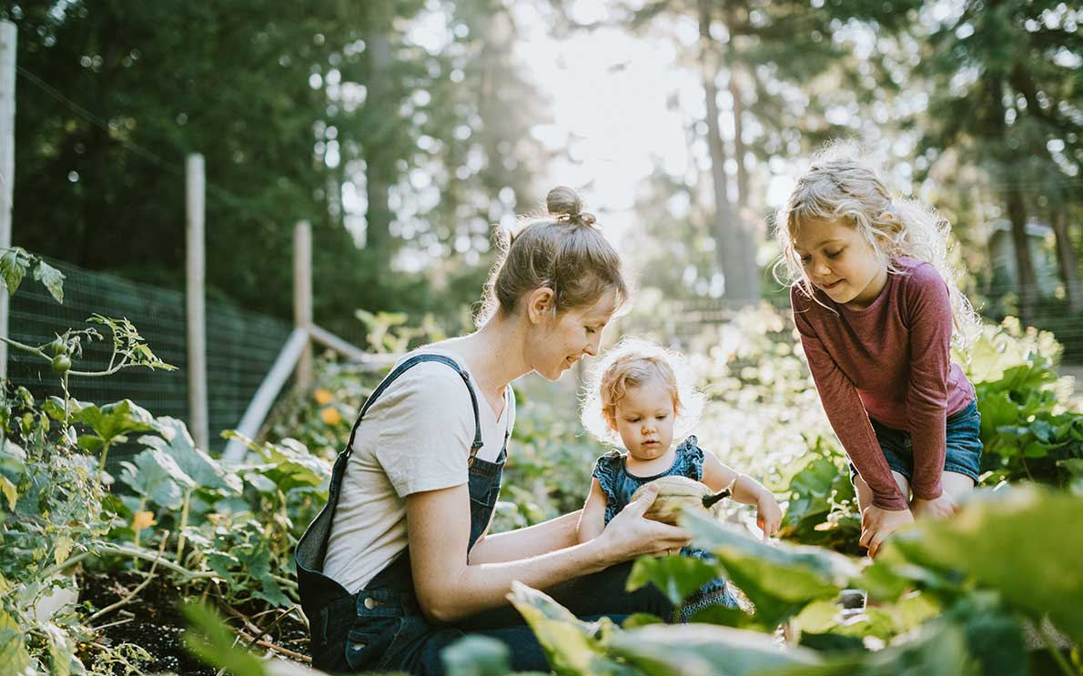 Mother and two little girls in a vegetable garden
