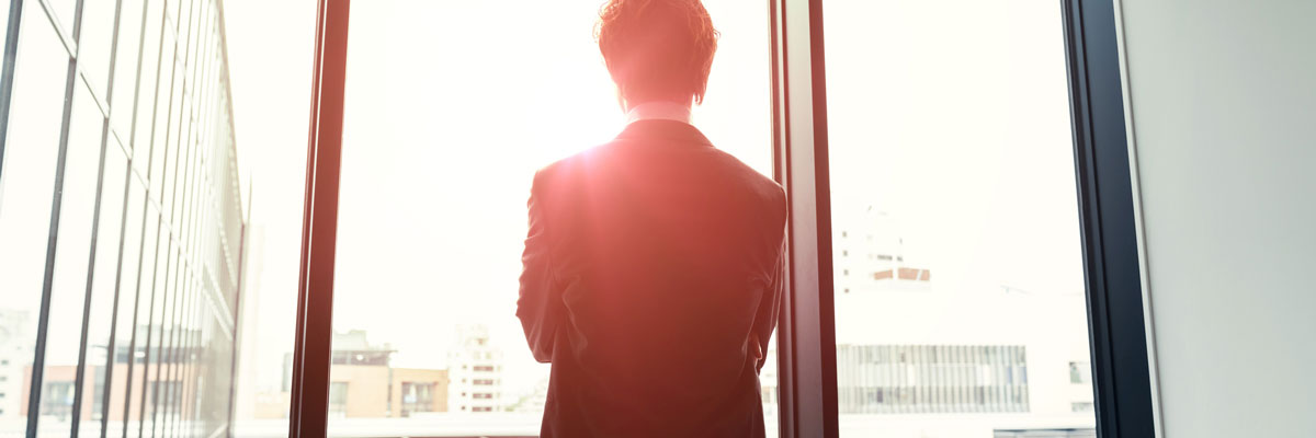 Man standing in front of a windowsill with the sun shining outlining silhouette