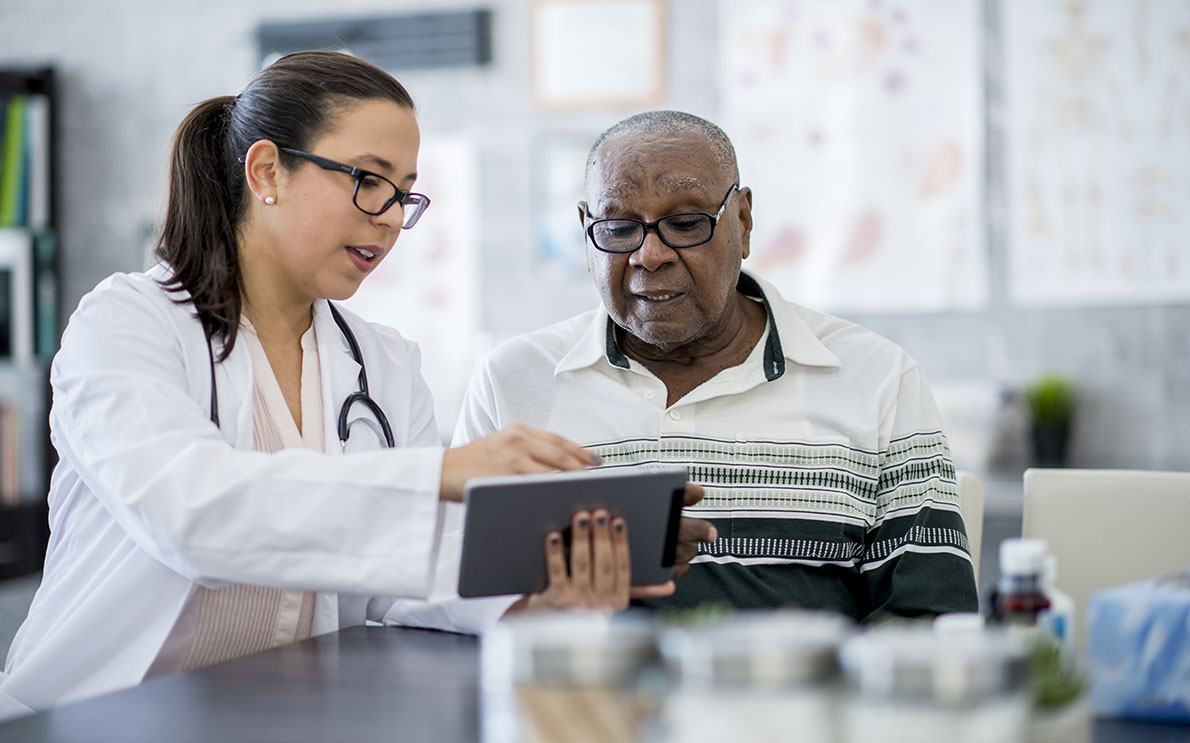 Female doctor showing elderly patient something on a digital tablet